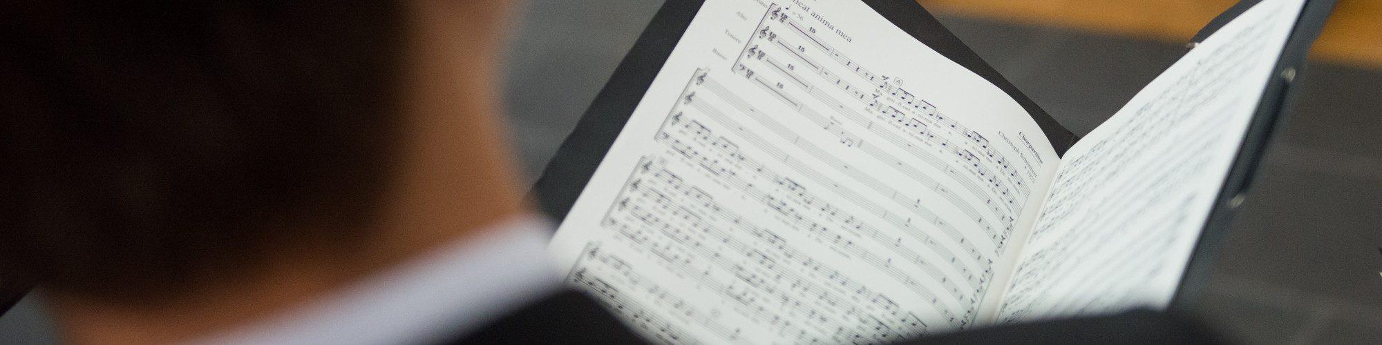 Die Nahaufname der Notenmappe eines Sängers des Vokalensembles vokalista